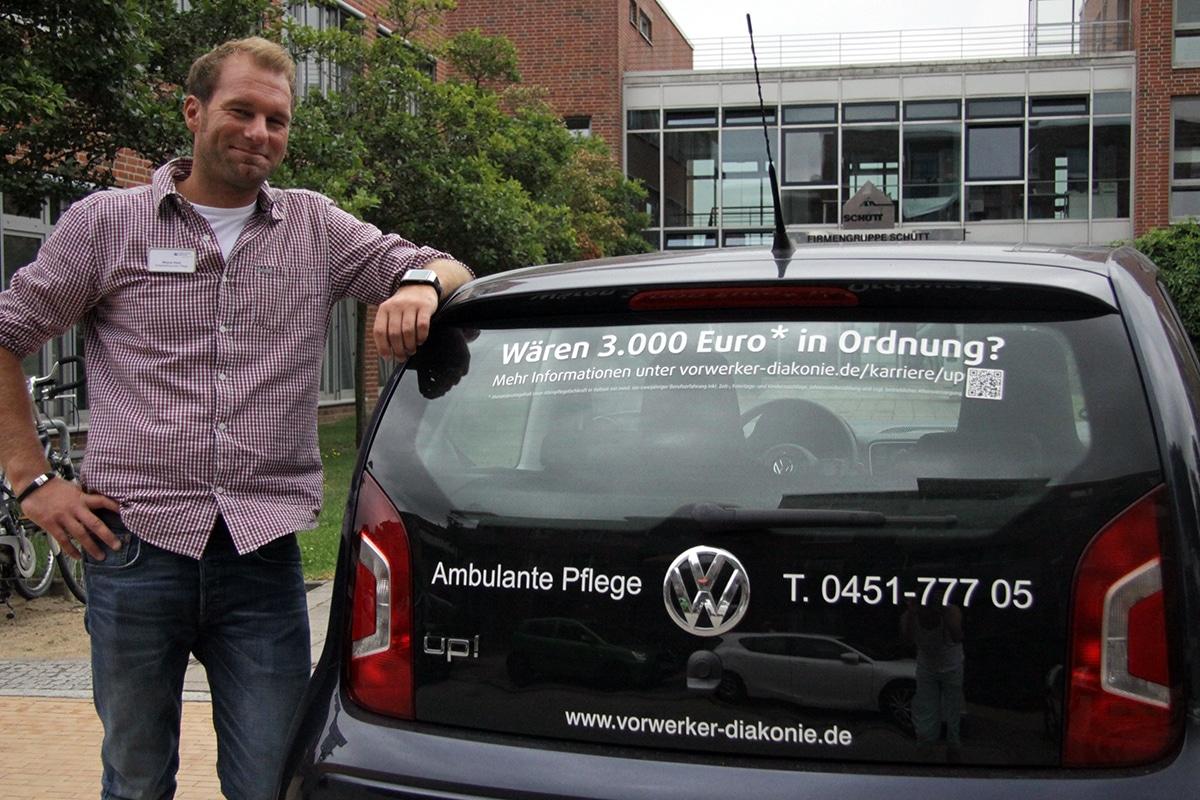 Wayne Dietz, Pflegedienstleitung in der Ambulanten Pflege der Vorwerker Diakonie, mit einem der fürs Personalmarketing eingesetzten Fahrzeuge