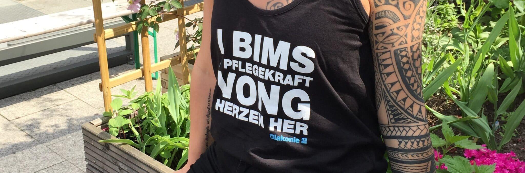 """Ausgefallenes Werbegeschenk für Jugendliche: Das Foto zeigt ein T-Shirt mit der Aufschrift """"I BIMS 1 PFLEGEKRAFT VONG HERZEN HER"""""""