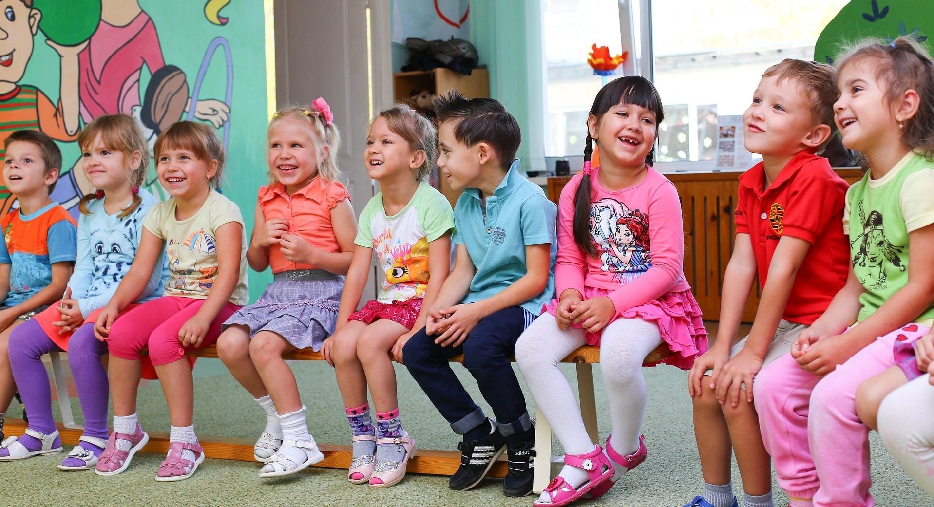 Kinder auf einer Bank zur Illustration von Muster-Stellenanzeigen für pädagogische Fachkräfte. Damit können Arbeitgeber Erzieher finden.